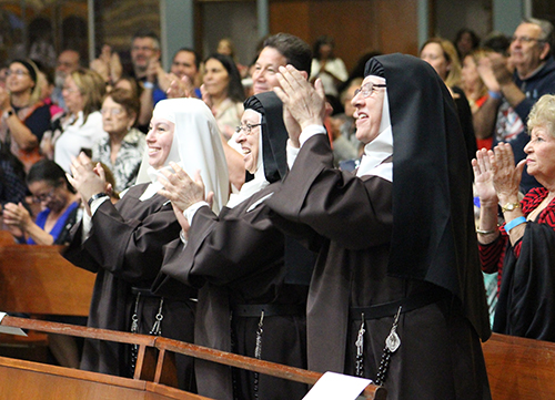 When the nuns applaud, you know it was great: From left: Discalced Carmelite novice Ashley Amalia Osorio, Mother Maricela de Jesus Maria, and Mother Mery Alba de Jesus applaud the music ministry group Jésed who performed at their contemplative benefit concert Nov. 6 at Immaculate Conception Church. The funds collected will go towards the completion of their  Monastery of the Most Holy Trinity in Homestead.