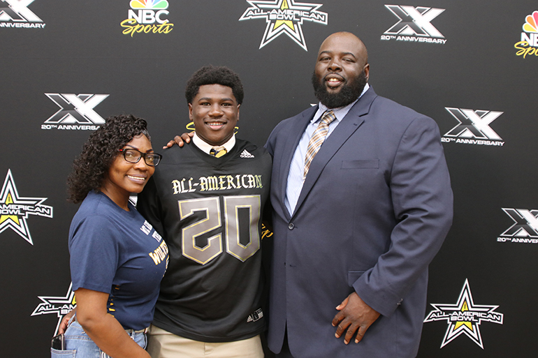 Belen Jesuit Don Chaney Jr. poses with his parents, Williesha and Don Chaney Sr., after receiving his All-American Bowl football jersey.