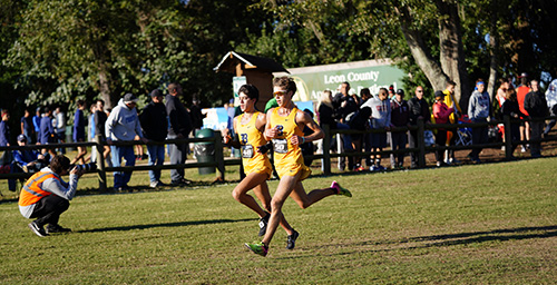 Belen Jesuit's Diego Gomez (#48) and Adam Magoulas (#50) run side by side to finish third and fourth, respectively, to help their school win its record-breaking 11th state cross country championship.