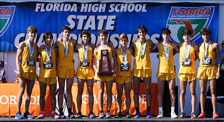 Belen Jesuit's cross country runners pose with their trophy and medals after winning the school's record-breaking 11th cross country state championship, Nov. 9, 2019, in Tallahassee.