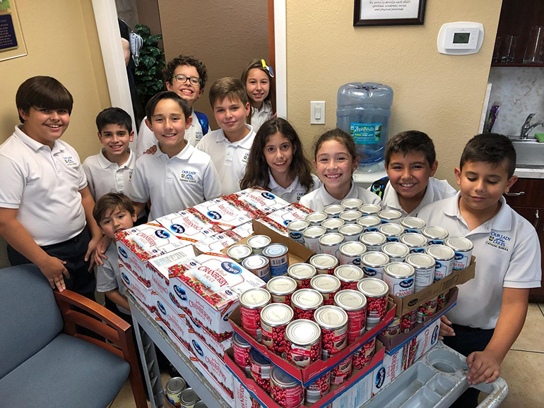 Fourth graders from Our Lady of the Lakes School pose with some of the food items donated to the parish and school's annual Thanksgiving drive. From Nov. 1 through Nov. 25, the Miami Lakes community collected enough to provide Thanksgiving meals to 710 families in neighborhoods surrounding Miami Lakes. The families received food and supermarket gift cards. The food bags included marshmallows, stuffing, dried beans, instant potatoes, corn, yams, cranberry sauce, peas, green beans, rice and macaroni and cheese.