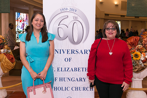 Tulia Aponte, left, and Yudy Romero, parishioners and members of the parish Hispanic community, pose in front of the banner announcing St. Elizabeth of Hungary's 60th anniversary. 