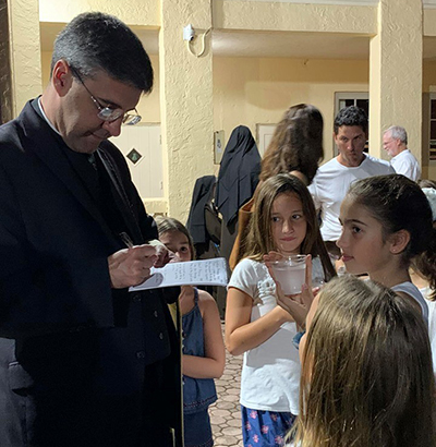 Father Manny Alvarez, pastor of Little Flower Church, Coral Gables, answers some questions from St. Theresa School's student-reporters after the dedication of the new Alumni Plaza.