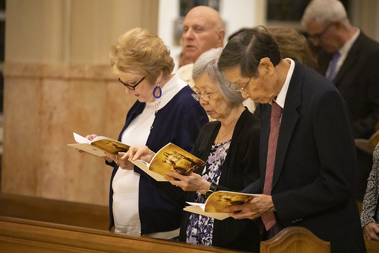 Truemin Chin, center, from the parish of Our Lady of Guadalupe in Doral, prays during the Thanks-for-Giving Mass celebrated at the Cathedral of St. Mary, Nov. 23, 2019. Chin received the One in Faith award from Archbishop Thomas Wenski.