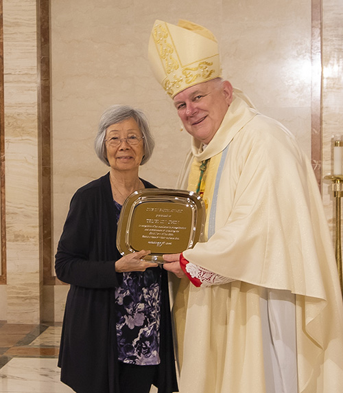 Archbishop Thomas Wenski gives Truemin Chin, from the parish of Our Lady of Guadalupe in Doral, the One in Faith award during the Thanks-for-Giving Mass celebrated at the Cathedral of St. Mary, Nov. 23, 2019.