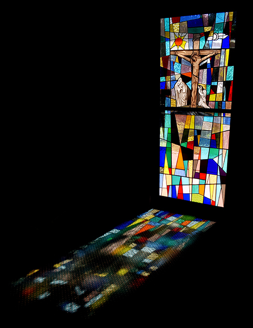A crucifixion window casts a multicolored shadow at St. Ambrose Church. The window is part of the church's Pietá Chapel, for private devotions.