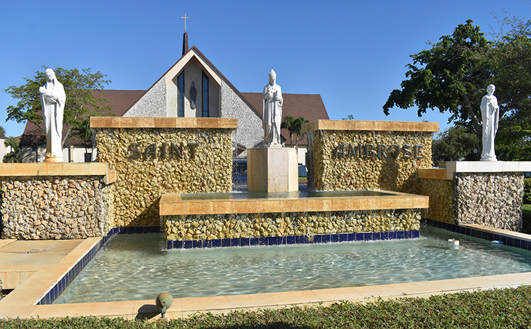 Statues of Mary, St. Ambrose and Joseph stand in front of a fountain in front of St. Ambrose Church in Deerfield Beach.