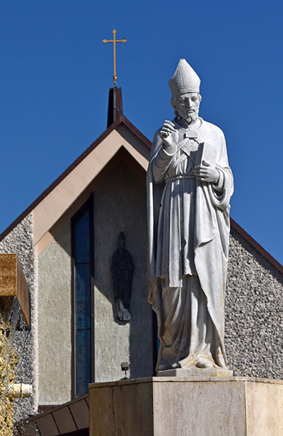 Statue of St. Ambrose stands in front of his namesake church in Deerfield Beach. A bas-relief of the saint can be seen on the church as well.