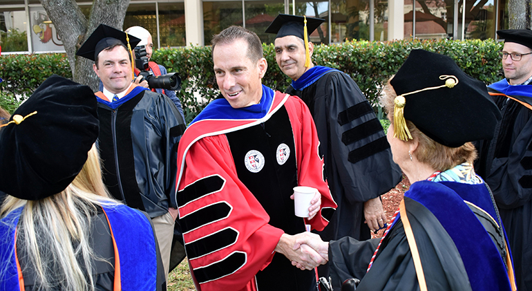 Mike Allen shakes hands with faculty members before his inauguration as president of Barry University.
