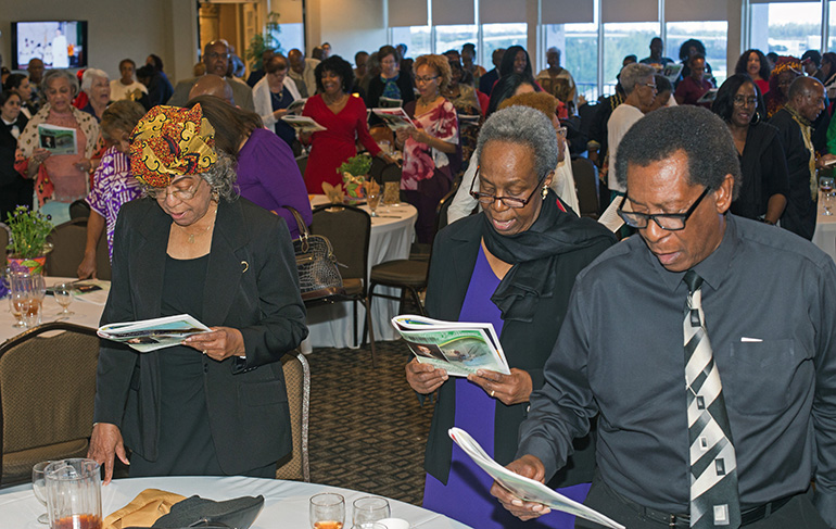 """From right, Jimmy Knowles, Bonita Smith and Margie Frances sing the Black National Anthem, """"Lift Every Voice and Sing,"""" at the close of the annual Black Catholic History Month awards luncheon, held at the Stadium Hotel in Miami Gardens, Nov. 16 2019."""