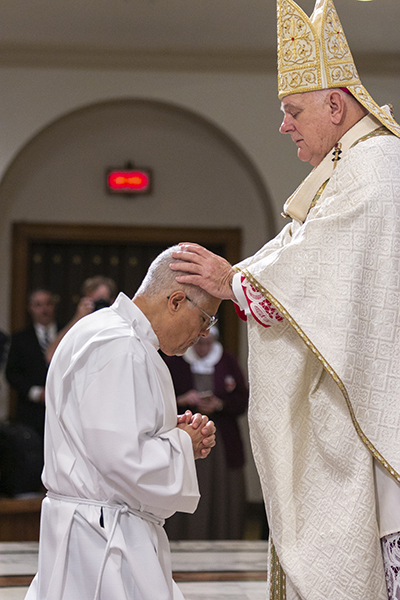 Archbishop Thomas Wenski lays hands on Enrique Ferrer of Mother of Christ parish in Miami, the moment of ordination.