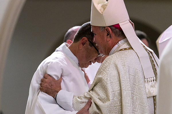 "At the conclusion of the ordination rite, Bishop Fernando Isern gives a ""fraternal kiss"" to his cousin, Deacon Jorge Matamala.