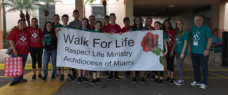 Chris Covone, far right, director of Campus Ministry at Archbishop Edward McCarthy High School, poses with students before starting the Walk for Life at the school Jan. 14, 2017. The school will host this year's walk on Saturday, Jan. 18.