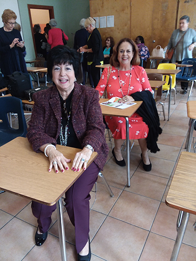 Elsa Reus, front, and former classmate Vivian Toscano sit one behind the other, as they did in Mrs. Hermo's French class 50 years ago. The alums made a return trip to Notre Dame Academy - now the Pierre Toussaint Haitian Center - Nov. 17, 2019.