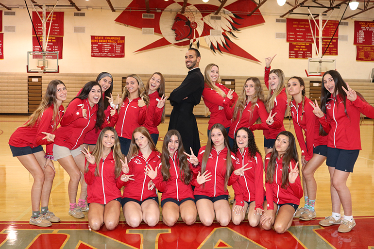 Piarist Father Ricardo Rivera has a fun moment with the Cardinal Gibbons dance team before practice.