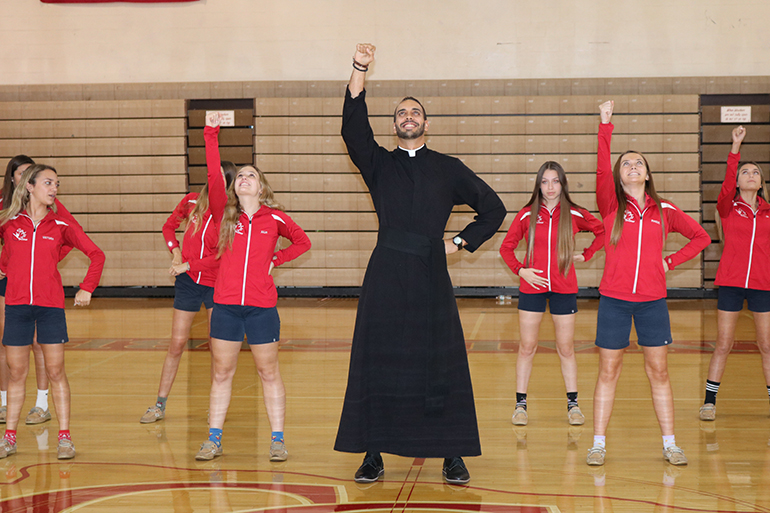 Piarist Father Ricardo Rivera shows off some dance moves with the Cardinal Gibbons dance team.