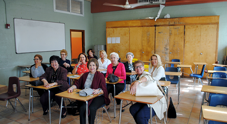 Elsa Reus, second from left, in front, and fellow Notre Dame Academy class of 1969 alumnae, sit in their old French classroom, which they found unchanged when they returned after 50 years to what is now Notre Dame d'Haiti Mission and Pierre Toussaint Haitian Catholic Center.