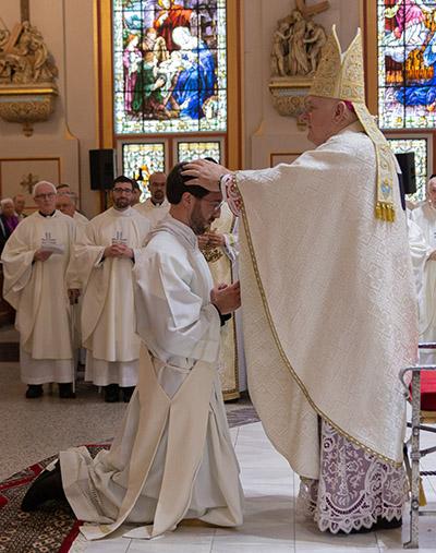 Archbishop Thomas Wenski lays hands on Jesuit Deacon Julio Minsal-Ruiz, ordaining him a priest. The ordination Mass took place Jan. 11, 2020, at Gesu Church in downtown Miami.