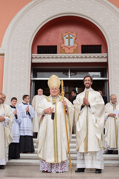 After the Mass, newly ordained Jesuit Father Julio Minsal-Ruiz poses with Archbishop Thomas Wenski at the main entrance to Gesu Church in downtown Miami.