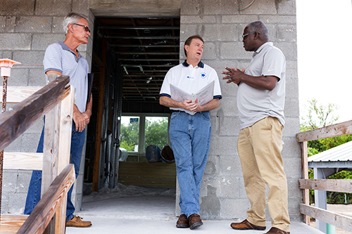 Jules Jones, right, CFO of Catholic Charities of the Archdiocese of Miami, makes a point during a walkthrough tour in Key West for a new Catholic Charities-sponsored St. Bede's Village workforce development facility in Key West, expected to be completed sometime in the summer of 2020.  With him are Key West-based architect William Horn, left, and Mark Shaughnessy, center, owner's representative for the building project.
