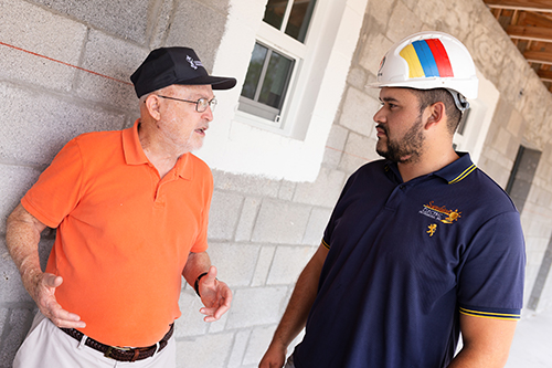 Tom Comerford, left, a member of Catholic Charities board of directors and St. John Neumann Parish in Miami, talks to a member of the building team during a recent tour of the construction site for a new Catholic Charities-sponsored St. Bede's Village workforce development facility in Key West, expected to be completed sometime in the summer of 2020.