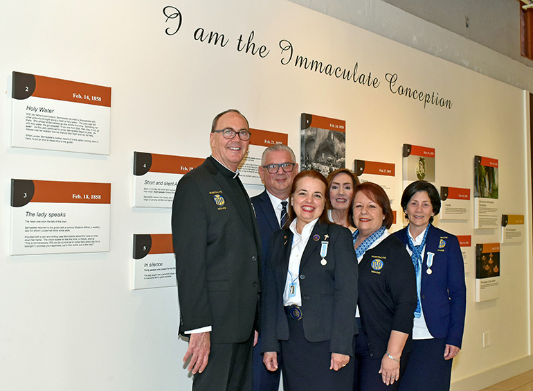 Members of Hospitalité de Miami gather at the timeline wall at Our Lady of Lourdes Church in Miami. Standing with Msgr. Kenneth Schwanger, the pastor, are, from left: Filippo Baglio, Mercy Baglio, Debra Bartkowski, Carmen Van Scoy and Fanny Garcia.