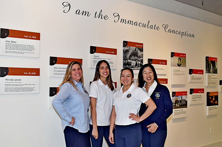 Members of Hospitalité de Miami gather at the timeline wall at Our Lady of Lourdes Church in Miami. From left are Cristina Fernandez, Daniella Perez, Gabriella Rodriguez and Michelle Rodriguez.