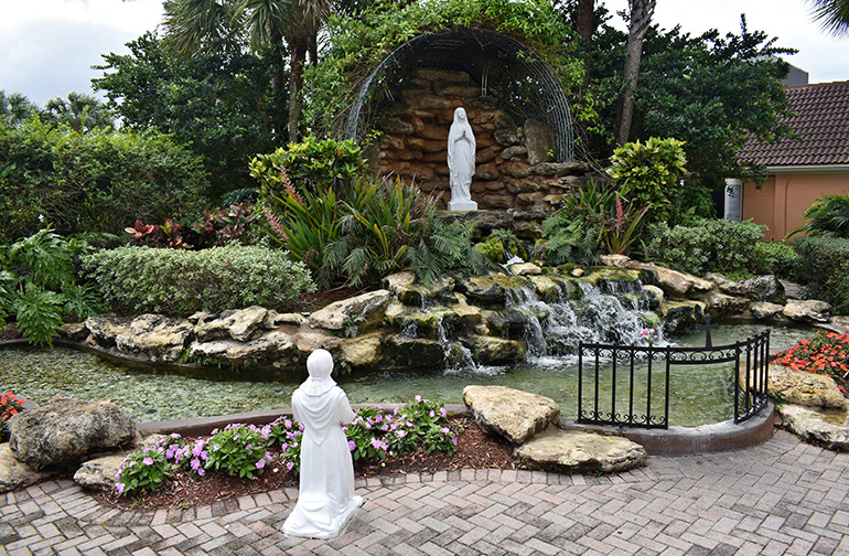A statuette of St. Bernadette kneels at a grotto and waterfall meant to evoke the shrine at Lourdes, France.