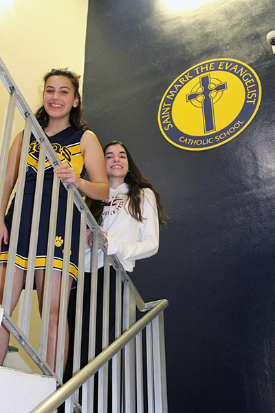 St. Mark the Evangelist School seventh graders Olivia Perez and Katherine Cue pose in one of the stairways of the school. Olivia and Katherine worked together to create a video history of their school, now celebrating its 25th anniversary, which was screened at the school gala held Jan. 24, 2020.