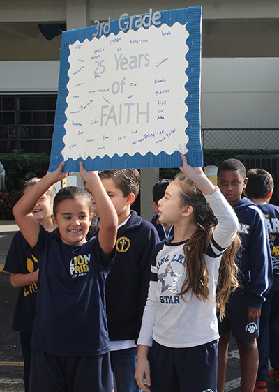 Two St. Mark School third graders hold up a poster signed by all of their classmates, celebrating the school's 25th anniversary. On Jan. 24, 2020, students celebrated their school and also kicked off Catholic Schools Week with the first pep rally in the school's history.