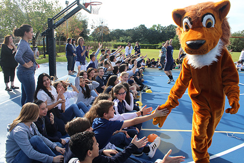 Here comes the Lion: St. Mark School's mascot hands out high-fives during the first pep rally in the school's history on Jan. 24, 2020. The celebration coincided with the school's 25th anniversary, and also kicked off Catholic Schools Week.