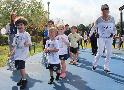 St. Mark School Principal Teresita Wardlow accompanies PreK4 students as they depart the school basketball court after the pep rally held Jan. 24, 2020 to celebrate the school's 25th anniversary.