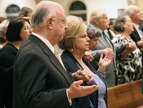 John and Beatriz Harriman hold hands during the Lord's Prayer at the wedding anniversary Mass celebrated at St. Mary Cathedral Jan. 25, 2020. The Harrimans are the founding couple of Matrimonios en Victoria (Marriages in Victory), a marriage movement in the Archdiocese of Miami, and were celebrating their 50th anniversary.