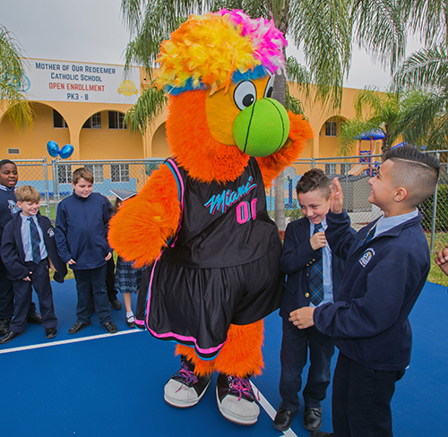 Fourth-graders Matthew Camert and Kevin Martinez high-five the Miami Heat's Burnie after the blessing of Mother of Our Redeemer's new basketball-volleyball court, Jan. 27, 2020.