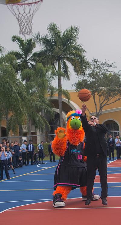 Mother of Our Redeemer's pastor, Father Juan Pedro Hernandez, shoots at the basket as Burnie, the Miami Heat mascot, looks on, part of the fun that followed the blessing of the school's new basketball-volleyball court, Jan. 27, 2020.