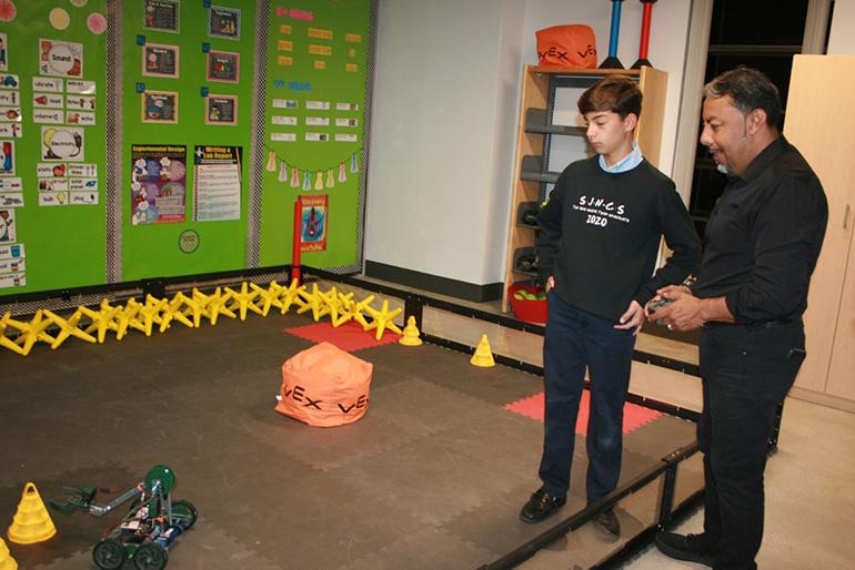 St. John Neumann eighth grade student Nicholas Fleites demonstrates the Vex robots to a guest.