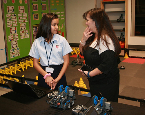 St. John Neumann seventh grade student Priscilla Fernandez demonstrates the coding process for the Vex robots to school board member Monica Inguanzo.