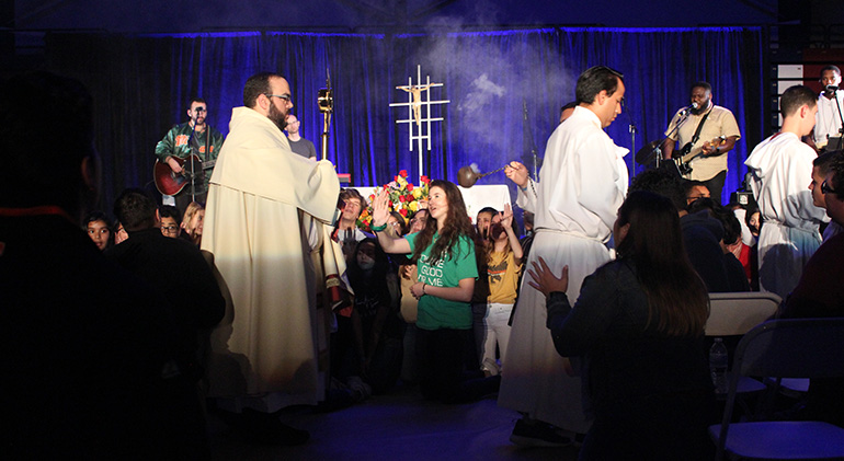 Father Matthew Gomez, parochial vicar at St. John Neumann Parish in Miami, leads the eucharistic procession and adoration that concluded this year's Mercy Night, held in the Fernandez Family Center of St. Thomas University, Jan. 31, 2020. Mercy Night attendees included teens, young adults and families.