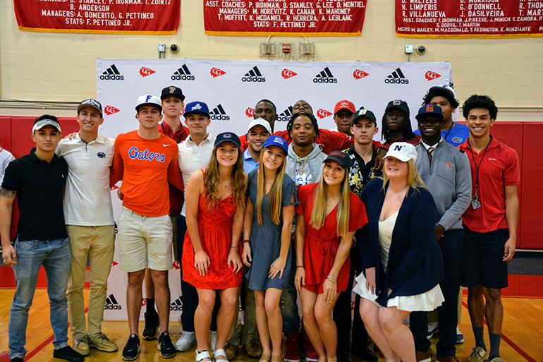 Nineteen of the 20 Cardinal Gibbons students who have signed National Letters of Intent to play their sports at the college level pose for a photo after the signing ceremony Feb. 5, 2020.