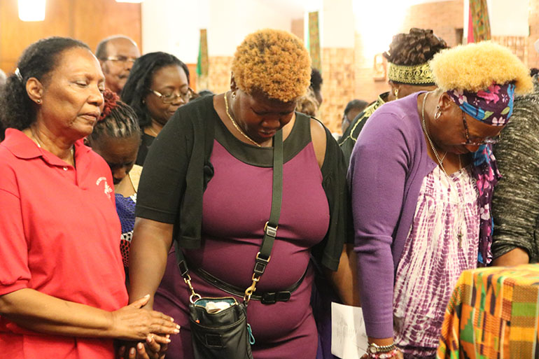 Faithful gather in prayer around the altar during Revival 2020's opening night, Feb. 16 at Holy Redeemer Church in Miami. Anita Victor is shown in the center wearing a purple dress. This was the first time she had participated in the annual event and appeared moved as she prayed.