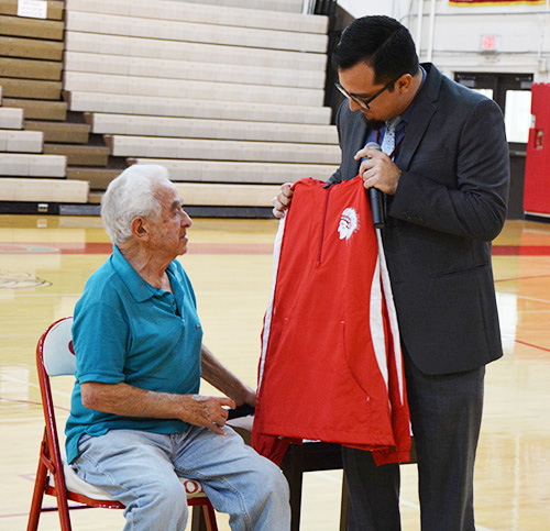 Cardinal Gibbons principal Oscar Cedeño presents a Gibbons fleece jacket to Holocaust survivor Bernard Igielski after he shared his story of survival with the high school's juniors and seniors.