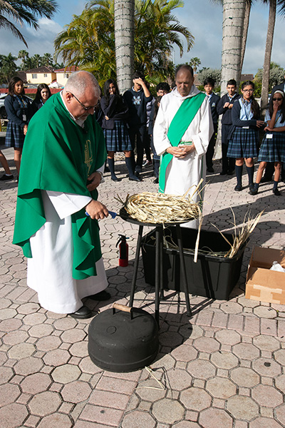 El P. Juan Hernández, párroco de la iglesia Mother of Our Redeemer, en Miami, prende fuego a las palmas mientras el Diácono Orlando Rojo y los estudiantes de la escuela observan.