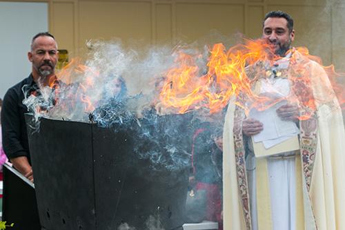 El P. Robert Ayala, párroco, y los estudiantes del programa de educación religiosa en la iglesia St. Matthew, en Hallandale Beach, observan mientras las palmas del Domingo de Ramos pasado se convierten en las cenizas del Miércoles de Ceniza de este año.