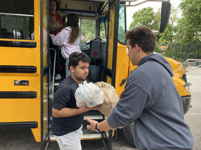 Msgr. Edward Pace High students fill a school bus with bagged meals they prepared for the homeless during Hungerfest, a pre-Lenten retreat where students, faculty and volunteers combine their own fasting with prayers, meal prepping and packing.