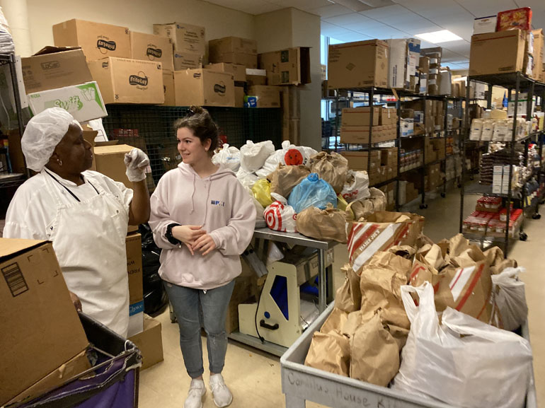 Helping the pantry that feeds: At the Camillus House pantry, a Hungerfest participant from Msgr. Edward Pace High listens to an employee. As part of their annual pre-Lenten retreat, Pace students delivered meals they prepared and packed.