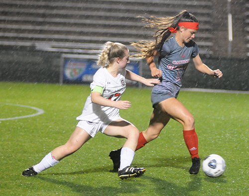 Cardinal Gibbons forward Ashley Nouss tries to break away from Bishop Kenny midfielder Gabi Iuliano during the first half of their FHSAA Class 4A girls soccer state-championship match, Feb. 26, 2020 at Spec Martin Stadium in DeLand. Bishop Kenny won the match 2-1.