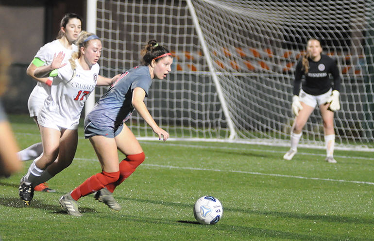 Cardinal Gibbons midfielder Gianna Mitchell, right, looks for an open player while moving away from Bishop Kenny's Gabi Iuliano during the first half of the Feb. 26, 2020 FHSAA Class 4A girls soccer state-championship match at Spec Martin Stadium in DeLand.