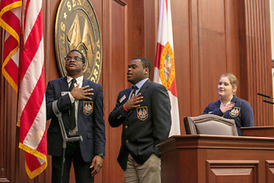 Brothers Christopher Sykes, left, and Corey Sykes of Monsignor Pace High pledge allegiance to the American flag during a recent internship in Tallahassee.