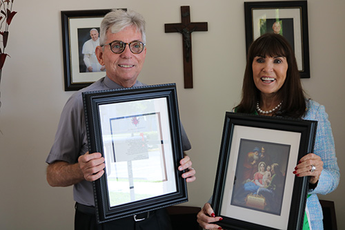 Catherine Wiley, founder of the Catholic Grandparents Association, presents Father Michael Greer, pastor of Assumption Parish in Lauderdale-By-The-Sea, with an image of the Holy Family and a framed prayer for grandparents. Father Greer hosted a meeting at his church, Feb. 20, 2020, to launch the new grandparents ministry in the Archdiocese of Miami.