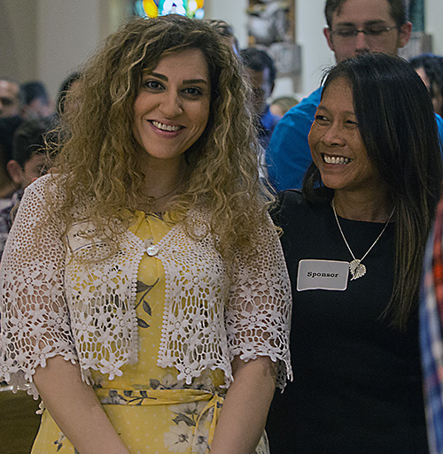 Neda Kalhor, 32, left, a catechumen from St. Bonaventure Church in Davie, stands with her sponsor, Tina McMahon, before signing the Book of the Elect at one of the two Rite of Election ceremonies held March 1, 2020, at St. Mary Cathedral.